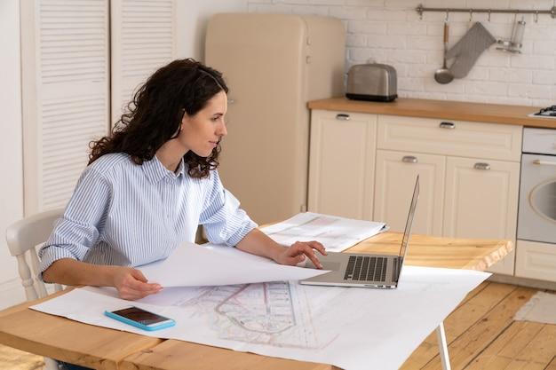 Mulher designer trabalha em casa com o laptop na mesa da cozinha