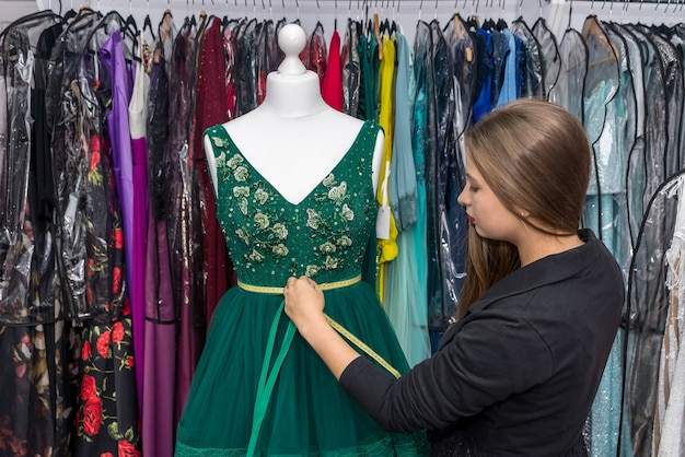 Mulher designer trabalhando com vestido e fita métrica