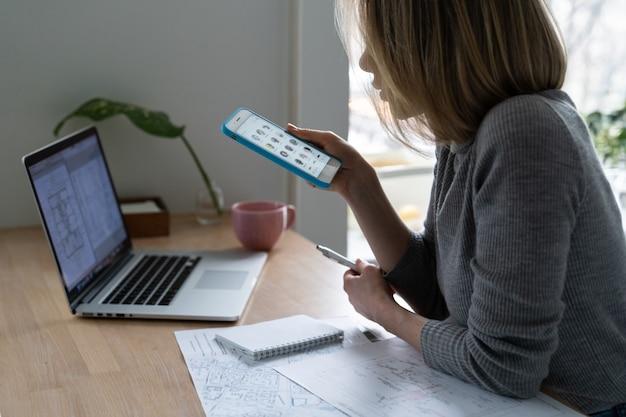 Mulher designer usando smartphone, faz uma pausa no trabalho e ouve um palestrante no clube