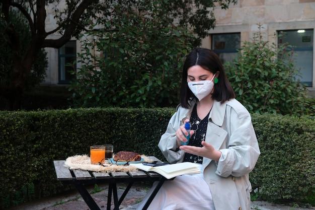 Mulher desinfetando as mãos em um terraço