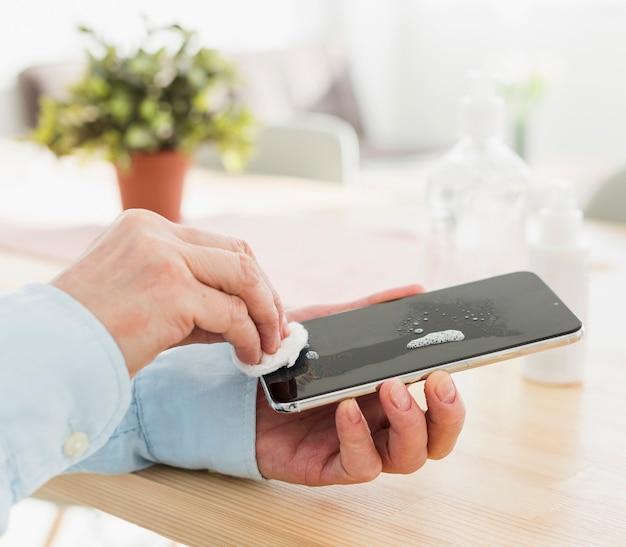 Mulher desinfetar o telefone em casa