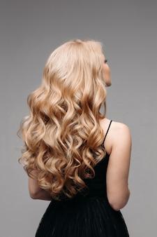 Mulher deslumbrante com cabelo loiro ondulado perfeito.