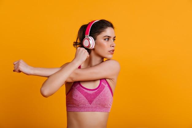 Mulher deslumbrante com fones de ouvido fazendo exercícios aeróbicos