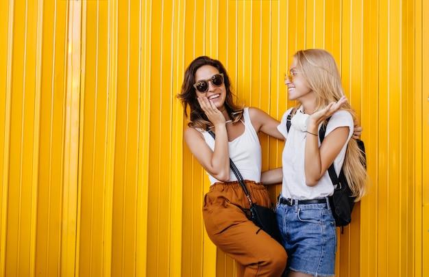 Mulher deslumbrante de cabelos castanhos de óculos, rindo com a amiga loira.
