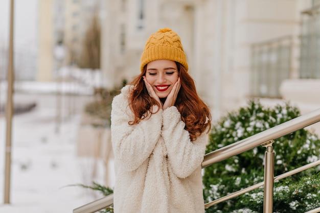 Mulher deslumbrante de gengibre posando com um sorriso sincero num dia de inverno. menina caucasiana positiva se divertindo em dezembro.