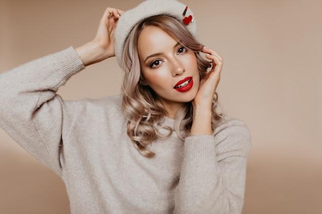 Mulher deslumbrante de olhos castanhos posando com um suéter bege gigante