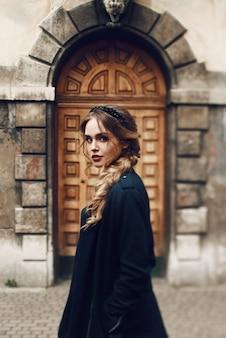 Mulher deslumbrante em casaco preto coloca diante de um edifício antigo