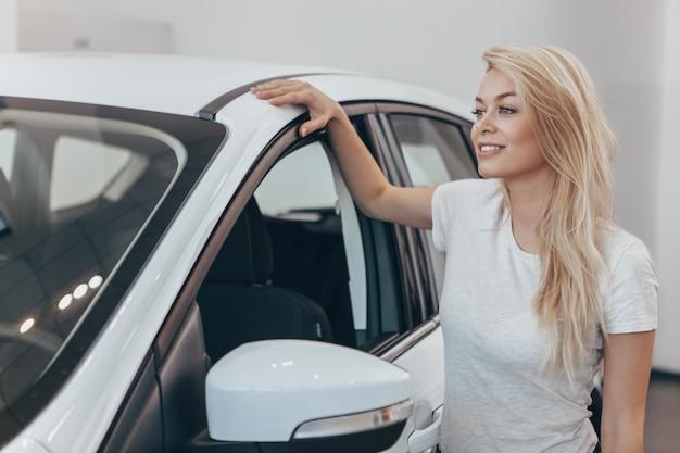 Mulher deslumbrante, olhando para longe em pé perto de seu novo automóvel na concessionária.