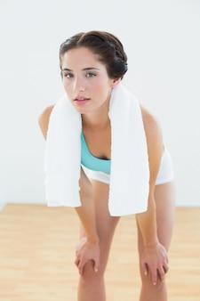 Mulher despedida com uma toalha em volta do pescoço no estúdio de ginástica