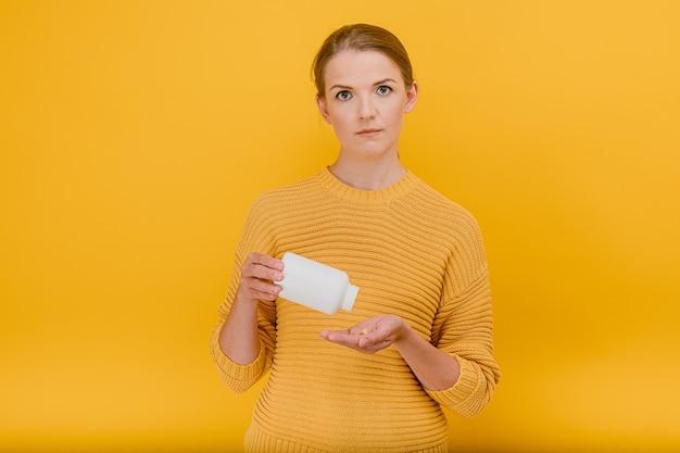 Mulher despeja comprimidos de um tubo com vitaminas na palma da mão com expressão duvidosa