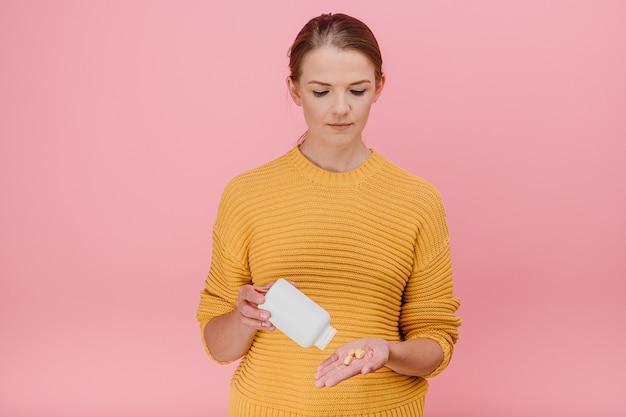 Mulher despeja comprimidos de um tubo com vitaminas na palma da mão