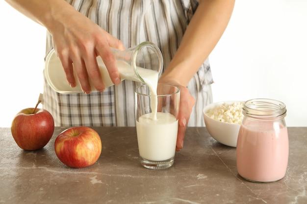Mulher despeja leite na mesa cinza com maçãs, iogurte e queijo cottage