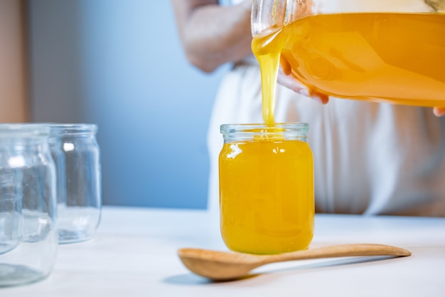 Mulher despeja mel em potes transparentes sobre uma mesa branca