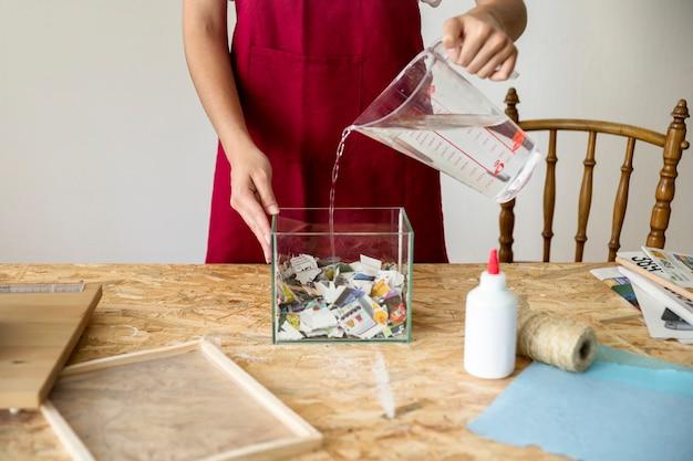 Mulher, despejar, água, em, recipiente, enchido, com, pedaços papel, em, oficina