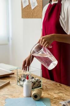 Mulher, despejar, água, em, recipiente vidro, com, torned, papel