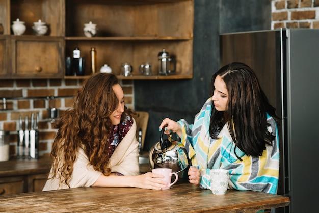Mulher, despejar, chá, para, dela, amigo feminino, em, cozinha