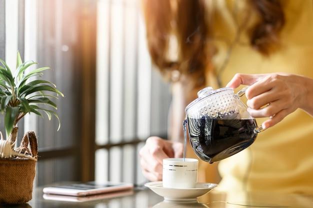 Mulher, despejar, chá quente, de, vidro, panela chá, para, branca, copo, enquanto, sentando, em, café