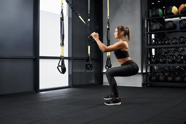 Mulher desportiva a agachar-se com alças de fitness