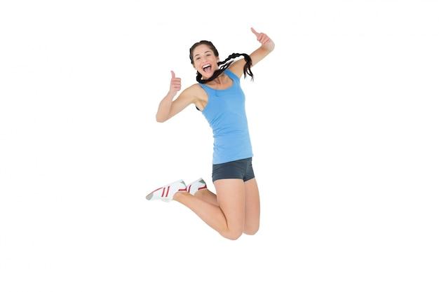 Mulher desportiva activa gesticulando polegares para cima