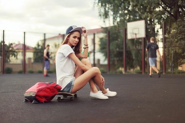 Mulher desportiva ao ar livre sentado no skate