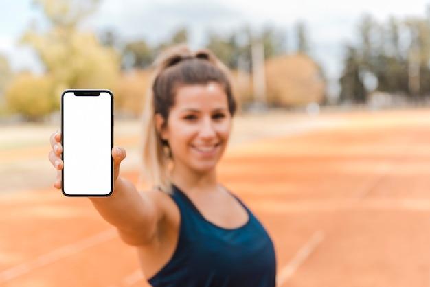 Mulher desportiva apresentando modelo de smartphone