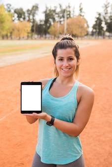Mulher desportiva apresentando modelo de tablet