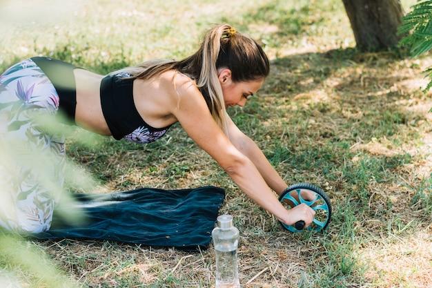Mulher desportiva ativa fazendo exercício com roda de rolo abs no parque