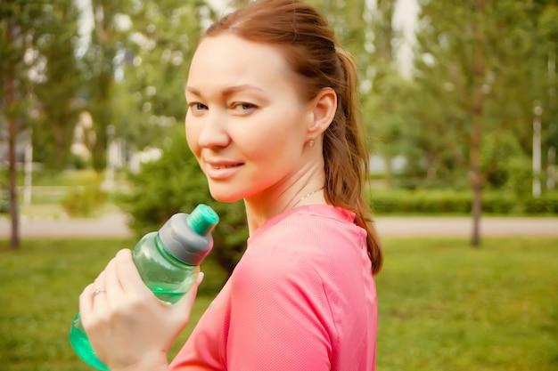Mulher desportiva ativa que guarda a garrafa após o treinamento