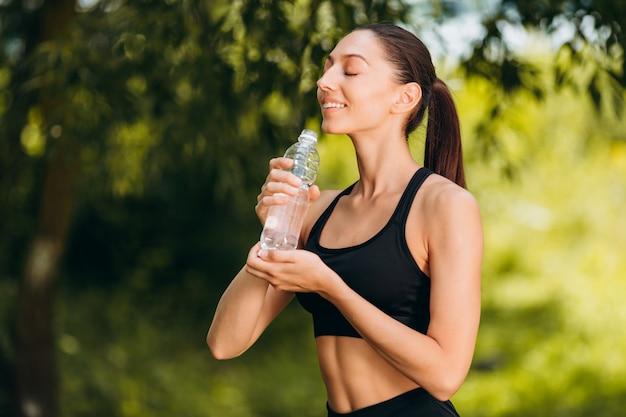 Mulher desportiva bebe água ao ar livre com prazer.
