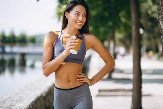Mulher desportiva bebendo café no parque