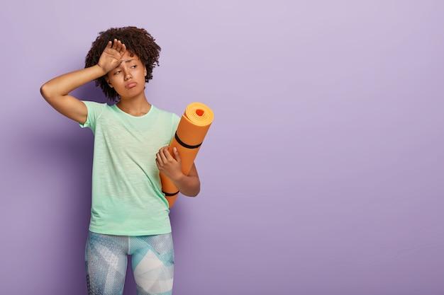 Mulher desportiva cansada com pele escura, sente cansaço após longas horas de treino, segura o tapete de fitness enrolado