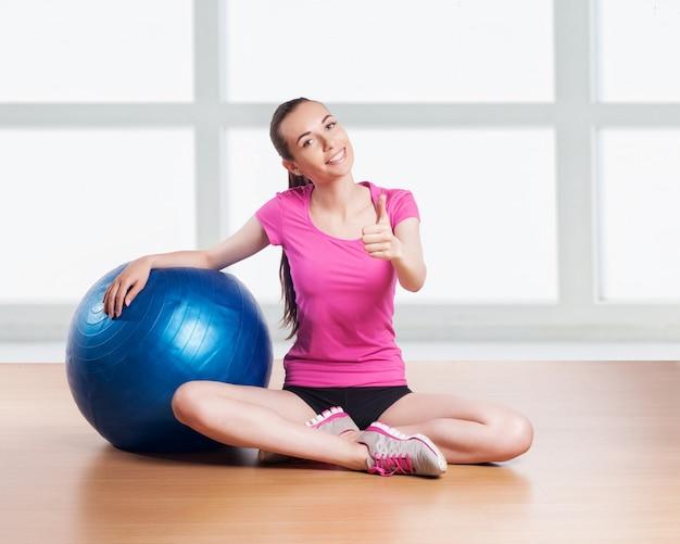 Mulher desportiva com bola de fitness.