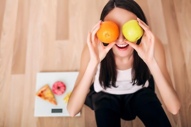 Mulher desportiva com escala e maçã verde e laranja