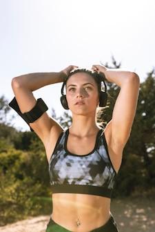 Mulher desportiva com fones de ouvido se preparando para correr