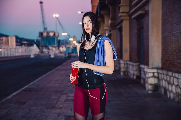 Mulher desportiva com garrafa olhando para a câmera