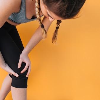 Mulher desportiva com joelho ferido