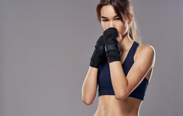 Mulher desportiva com luvas de boxe em fundo cinza.
