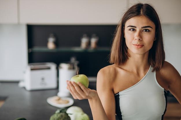 Mulher desportiva com maçã na cozinha