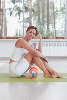 Mulher desportiva com rolo de espuma sentada no tapete no pavilhão desportivo