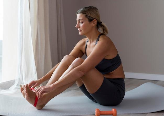 Mulher desportiva com roupa azul de fitness vista lateral