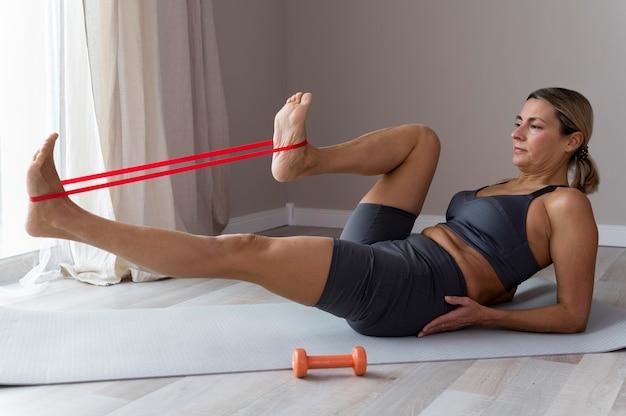 Mulher desportiva com roupa de fitness azul a fazer exercícios de perna