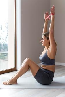 Mulher desportiva com roupa de fitness azul com os braços para cima