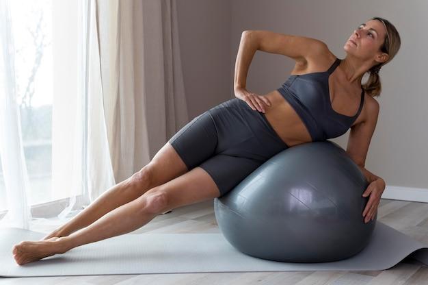 Mulher desportiva com roupa de fitness azul e bola de fitness