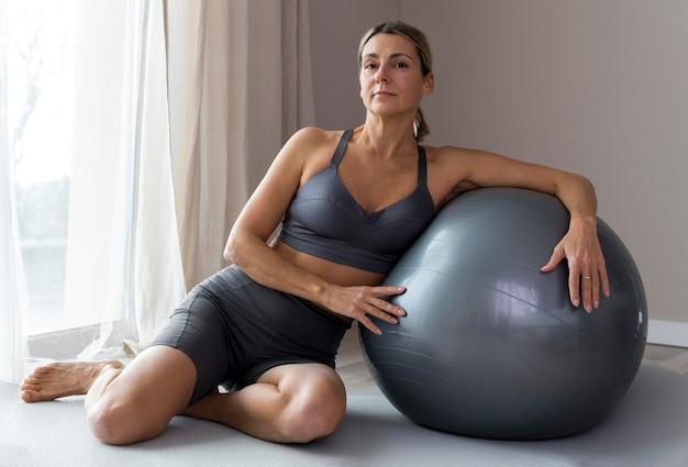 Mulher desportiva com roupa de fitness azul sentada ao lado de uma bola de fitness