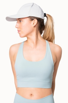 Mulher desportiva com roupa desportiva azul e boné virado para o lado