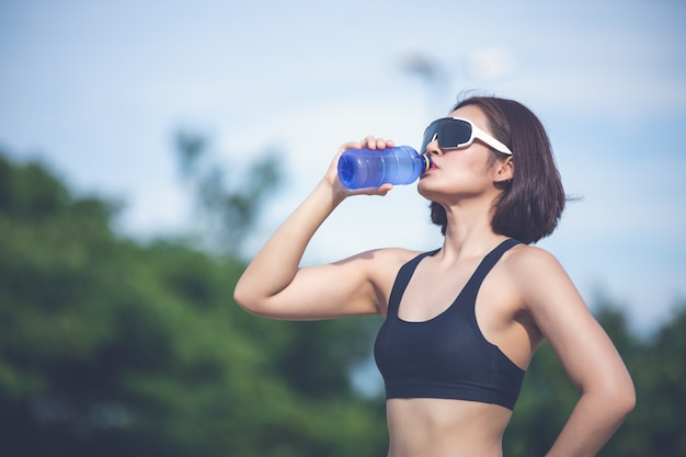 Mulher desportiva como água potável ao ar livre depois de correr em dia ensolarado