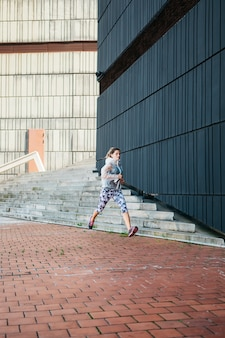 Mulher desportiva correndo em ambiente urbano