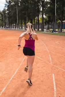 Mulher desportiva correndo na pista do estádio