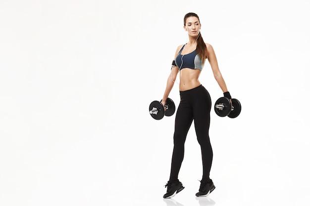 Mulher desportiva da aptidão nova nos fones de ouvido que treinam guardando pesos no branco.