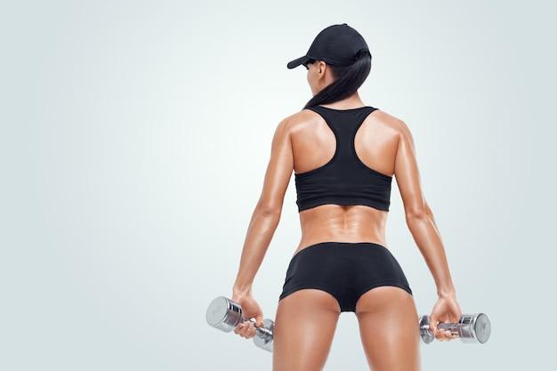 Mulher desportiva de aptidão no treinamento de bombeamento de músculos com halteres